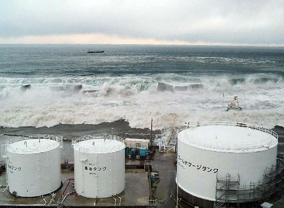 """HANDOUT RESTRICTED TO EDITORIAL USE - MANDATORY CREDIT """"AFP PHOTO / HO / TEPCO VIA JIJI PRESS"""" - NO MARKETING NO ADVERTISING CAMPAIGNS - DISTRIBUTED AS A SERVICE TO CLIENTS This picture, taken by Tokyo Electric Power Co (TEPCO) on March 11, 2011 and released on May 19, shows tsunami flowing over the sea walls as the mass of water powers towards TEPCO's Fukushima Daiichi nuclear power plant at Okuma town in Fukushima prefecture.   Workers briefly entered a reactor building at Japan's stricken Fukushima nuclear power plant to measure radiation levels and check for damage, the operator said. The investigation was part of work by Tokyo Electric Power Co. (TEPCO) to bring reactors at the complex to a stable cold shutdown by January at the latest. Photo: Tepco, AFP/Getty Images"""