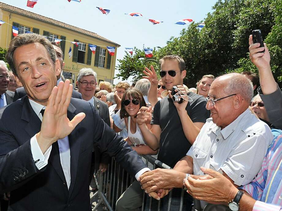 France's President Nicolas Sarkozy (L) shakes hand with people after a meeting with mayors of the Var departement in the French southeastern city of Bormes-les-Mimosas, on May 19, 2011. Photo: Gerard Julien, AFP/Getty Images