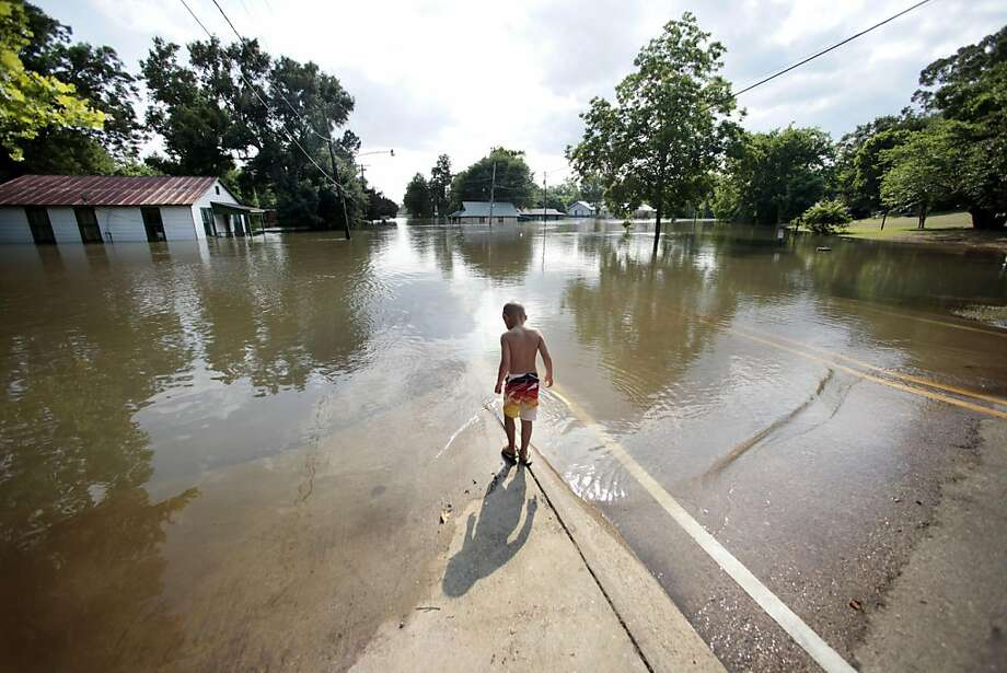 Landon Bonaventure, 5, walks to the edge of floodwater from the Mississippi River, that flooded a dozen homes and businesses, seen in background, in St. Francisville, La., Thursday, May 19, 2011. Photo: Gerald Herbert, AP