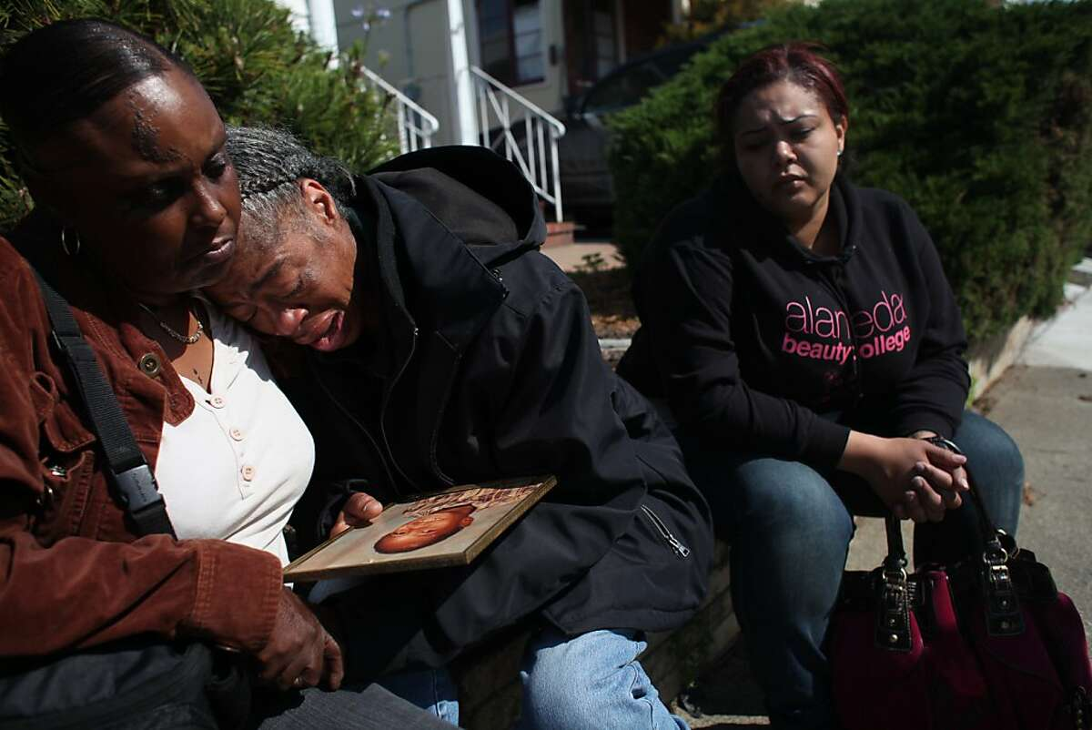 Mary Annette Cobb (center) of Oakland who's son, Antoine Jackson, was shot and killed in an officer involved shooting the evening before cries as she is supported by Helen Johnson (left) of Oakland as they sit on Curran Avenue along with Jackson's cousin, Lauren Chattman (right) in Oakland, Calif., Thursday, May 19, 2011. On Wednesday evening, officers reportedly shot two suspects at around 10:30 p.m. in the 3000 block of Curran Avenue in Oakland, Calif.