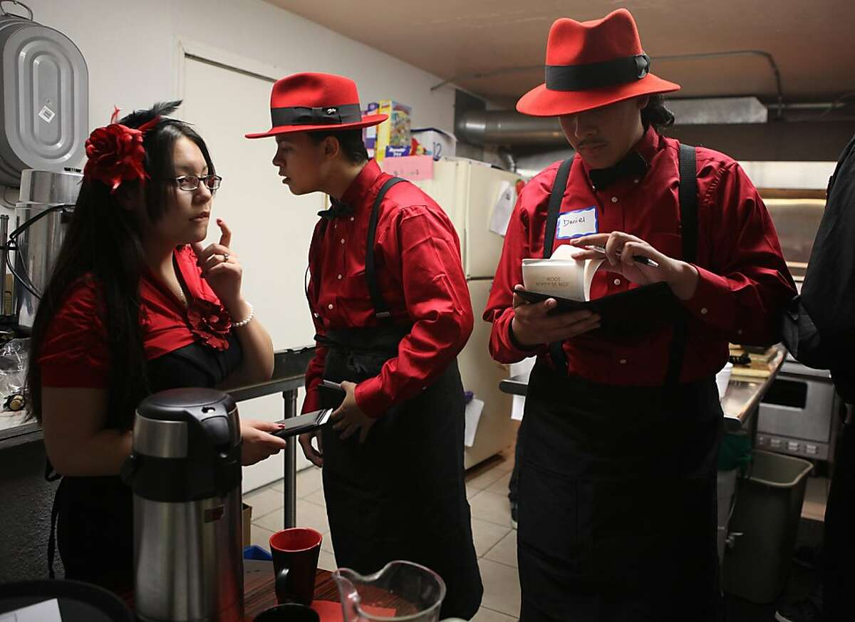 Interns Destiny Cravalho (left), 18 years old, and Andrew Urrutia (middle), 18 years old, in the kitchen while Daniel Bermudez (right), looks over orders as they host a swing dance dinner at Old Skool Cafe in San Francisco, Calif., on Friday, April 22, 2011. Old Skool Cafe is a program for youth that teaches them marketable culinary skills.