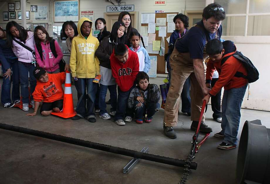 Gary Blos (second from right), plumber Department of Public Works, assists Jose Alberto (right), 9, 4th grader Tenderloin Community School, as he uses a snap cutter during an Open House at the Department of Public Works Operations Yard in San Francisco, Calif., Wednesday, May 18, 2011.  As part of National Public Works week celebrated every third week in May, the Department of Public Works (DPW) will hosts an Open House at its Operations Yard  for San Francisco fourth and fifth graders to demonstrate how the department cleans and greens the city. Photo: Lea Suzuki