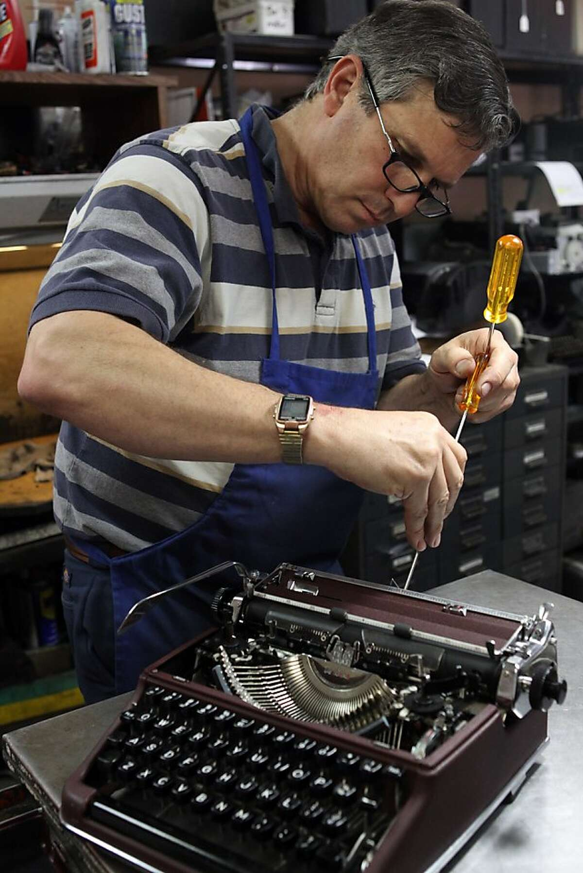 John Sansone, owner of Los Altos Business Machines, repairs a 1953 Olympia portable typewriter in his downtown Los Altos, CA shop on Thursday, May 5, 2011.