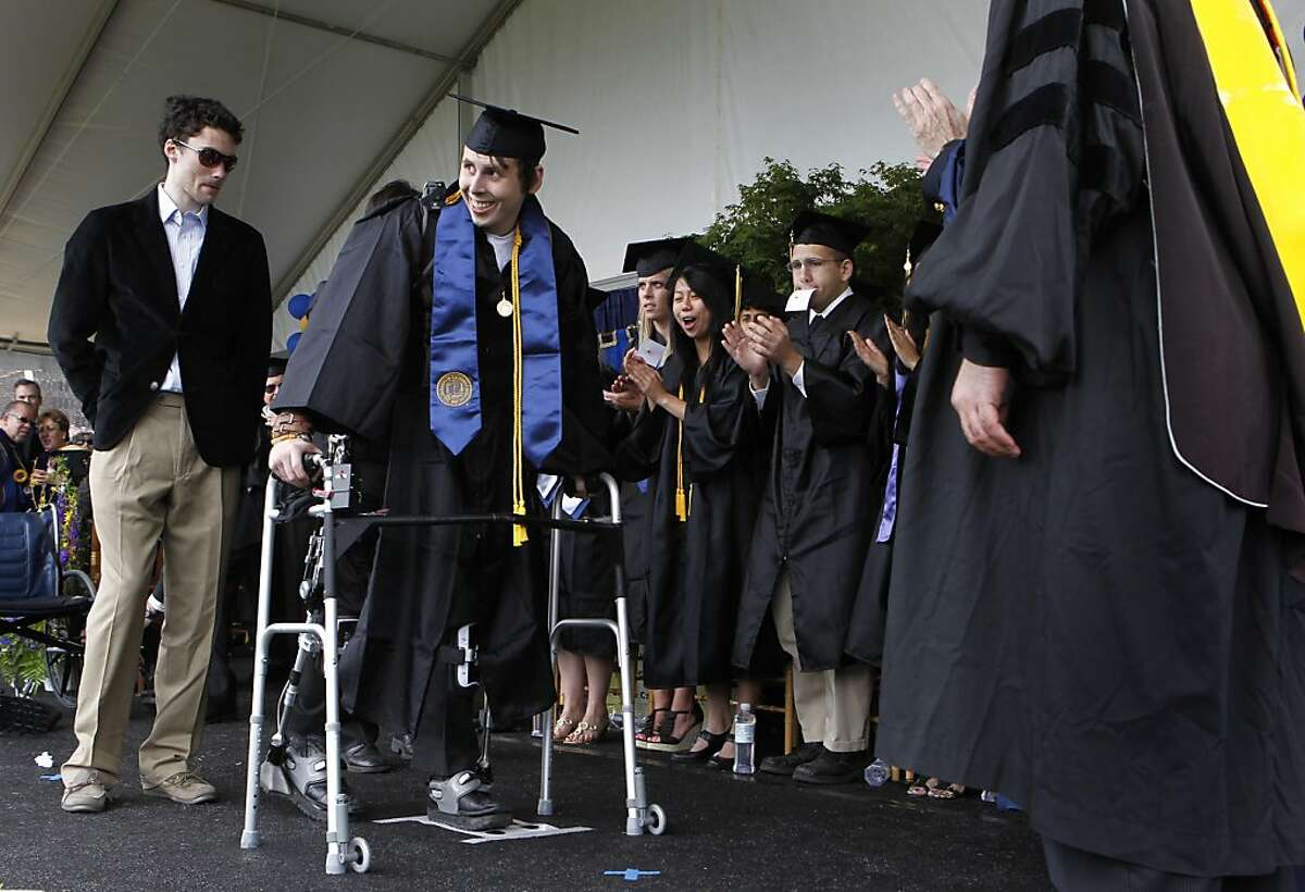 Austin Whitney walks across the stage strapped to exoskeleton legs during commencement ceremonies at UC Berkeley on Saturday. Whitney, who can no longer walk following an auto accident in 2007, walked across the stage wearing the device designed by a UC Berkeley engineering professor and a team of graduate students.