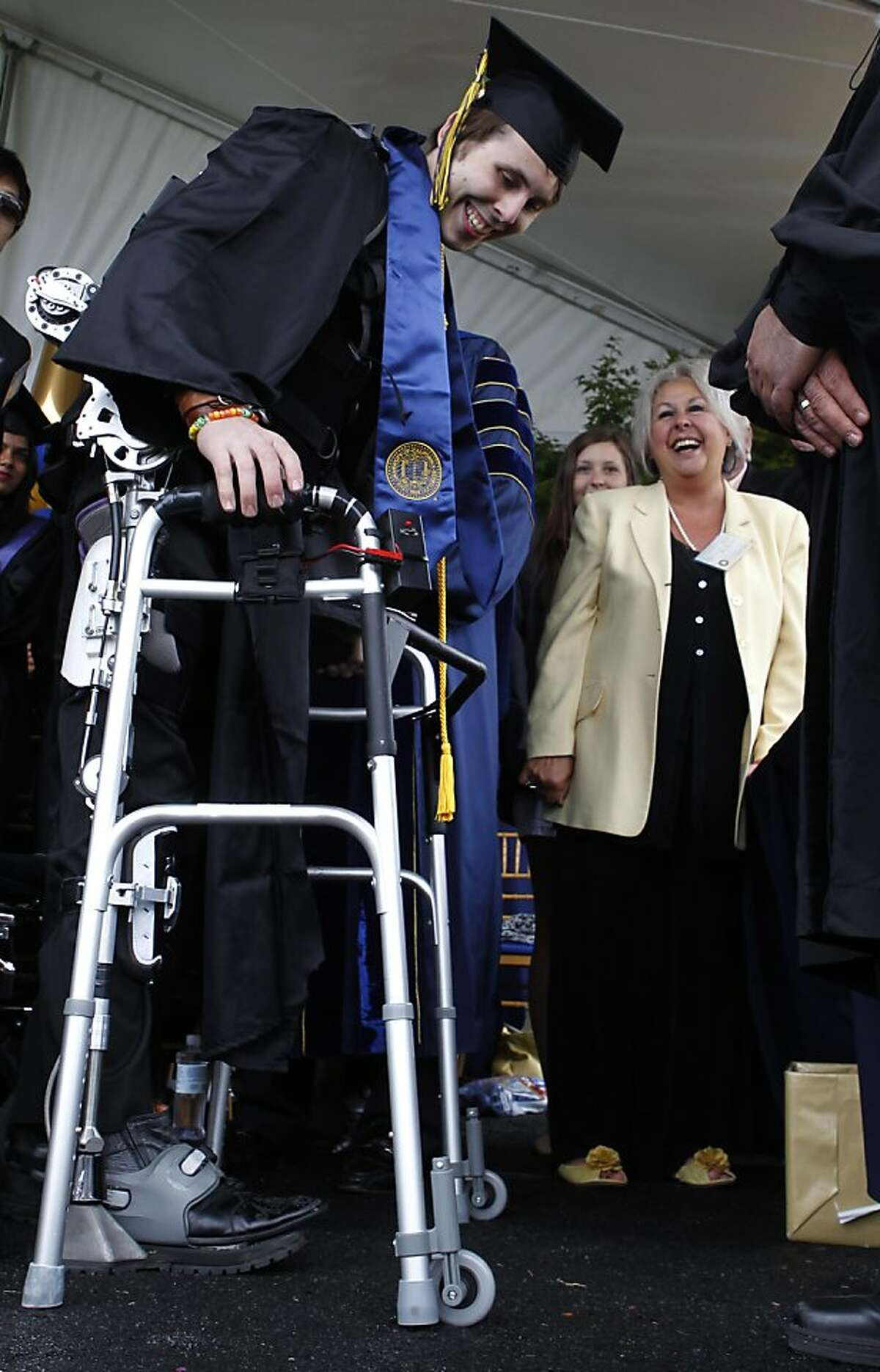 Lillian Whitney (right) watches her son Austin Whitney, who is paralyzed from the waist down, walk across the stage strapped to exoskeleton legs during commencement ceremonies at UC Berkeley on Saturday.