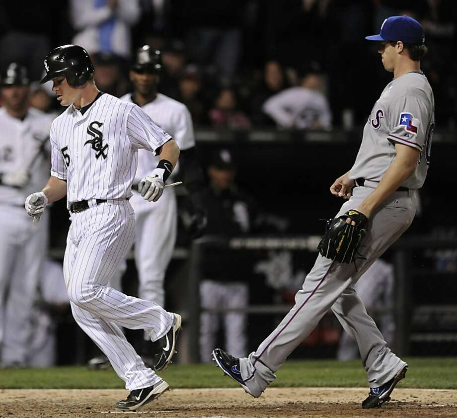 Chicago White Sox's Gordon Beckham left, scores on a wild pitch against the Texas Rangers during the eighth inning of a baseball game in Chicago, Tuesday, May 17, 2011. Chicago won 4-3. Photo: Paul Beaty, AP