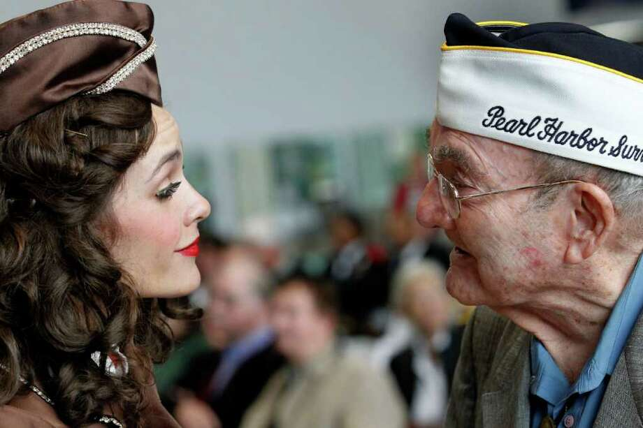 Pearl Harbor survivor Nolan Albarado reacts as a member of the Andrews Sisters styled group 'The Liberty Belles' planted a kiss on his cheek at a ceremony observing the 70th anniversary of the attack on Pearl Harbor, at the National World War II Museum in New Orleans, Wednesday, Dec. 7, 2011. Photo: Gerald Herbert, Associated Press / AP
