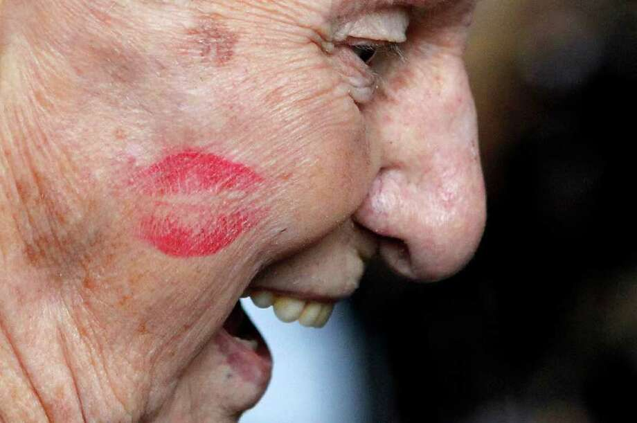 A lipstick mark is seen planted on the cheek of Pearl Harbor survivor James Cook by a member of the Andrews Sisters' styled 'Liberty Belles,' at a ceremony to observe the 70th anniversary of the attack on Pearl Harbor, at the National World War II Museum in New Orleans, Wednesday, Dec. 7, 2011. (AP Photo/Gerald Herbert) Photo: Gerald Herbert, Associated Press / AP