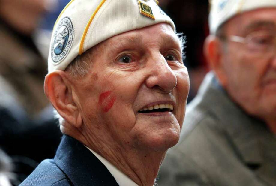 "Pearl Harbor survivor James Cook smiles after getting a kiss on the cheek from a member of the Andrews Sisters-styled ""Liberty Belles"" at a ceremony observing the 70th anniversary of the attack on Pearl Harbor at the National World War II Museum in New Orleans, Wednesday, Dec. 7, 2011. Photo: Gerald Herbert, Associated Press / AP"
