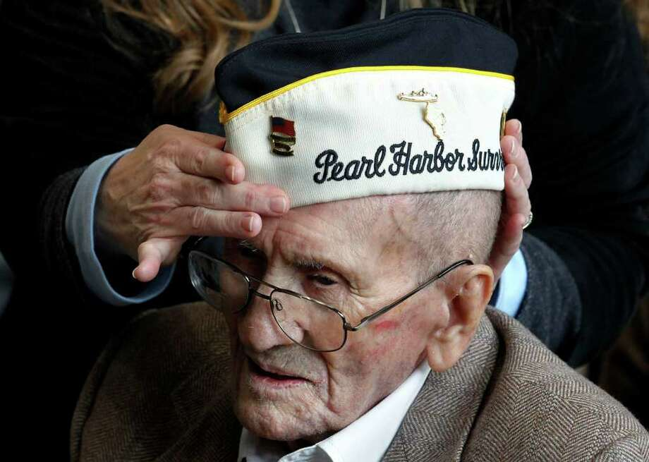 Ruth Melanson helps put on the hat of her father, Pearl Harbor survivor Evan Brasset, at a ceremony observing the 70th anniversary of the attack on Pearl Harbor, at the National World War II Museum in New Orleans, Wednesday, Dec. 7, 2011. Photo: Gerald Herbert, Associated Press / AP