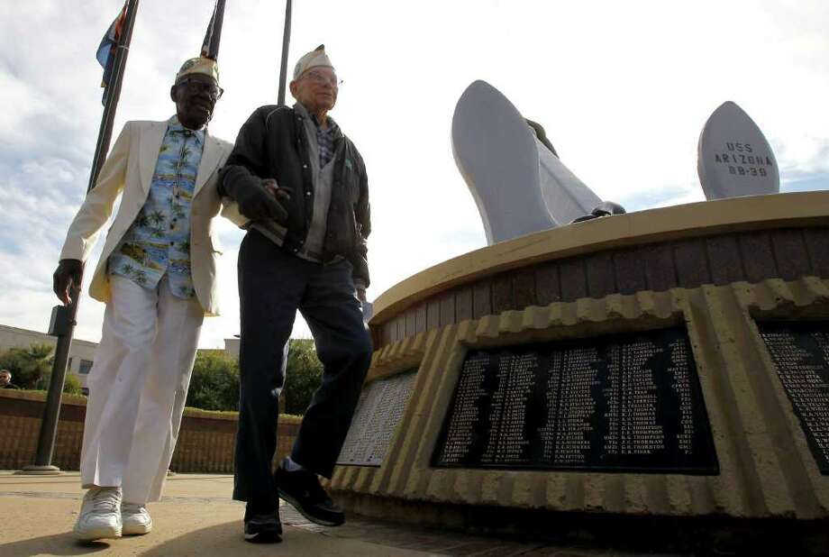 Pearl Harbor Survivors Nelson Mitchell, 91, left, and Marvin Rewerts, 89, right, walk past the USS Arizona Memorial after placing a wreath there at the Peal Harbor Remembrance Day ceremonies Wednesday, Dec. 7, 2011, in Phoenix. Photo: Ross D. Franklin, Associated Press / AP