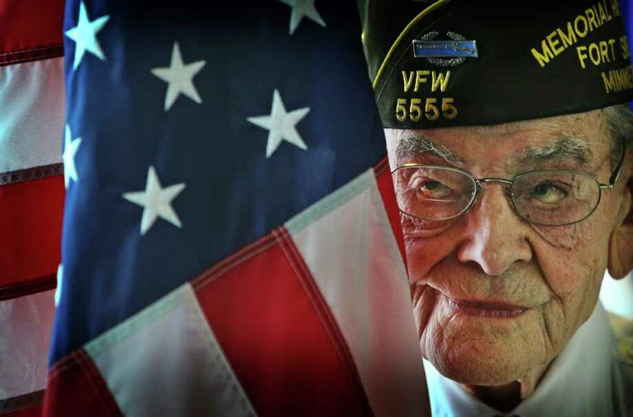 World War II Army veteran Quentin DeNio, 92, of South Minneapolis, the American flag bearer for the Fort Snelling National Cemetery Memorial Rifle Squad, participates in a ceremony to commemorate the 70th anniversary of the attack on Pearl Harbor at the Veterans Service Building in St. Paul, Minn., Wednesday, Dec. 7, 2011. Photo: David Joles, Associated Press / The Star Tribune