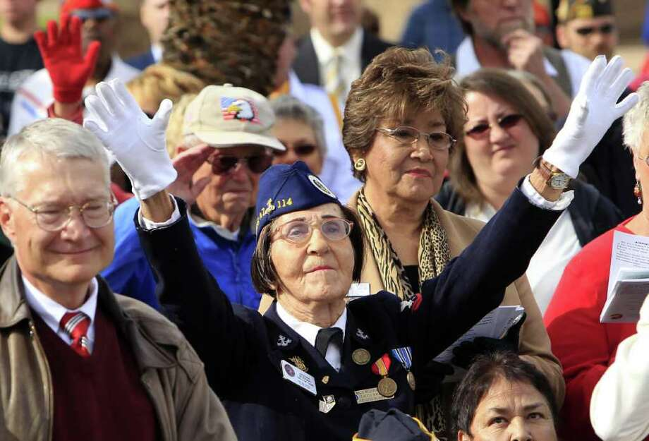 "World War II Veteran with the Navy WAVES, Helen Coyte, raises her arms as the 108th Army Band performs ""Anchors Aweigh"" at the Peal Harbor Remembrance Day ceremonies Wednesday, Dec. 7, 2011, in Phoenix. Photo: Ross D. Franklin, Associated Press / AP"