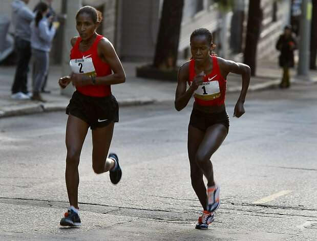 Lineth Chepkurui (right) who eventually won the women's race passed Mamitu Daska on the Hayes Street hill. The 100th running of the Bay to Breakers race in San Francisco, Calif. featured thousands of people and a few new rules to tame past turmoil Sunday May 16, 2011. Photo: Brant Ward, The Chronicle