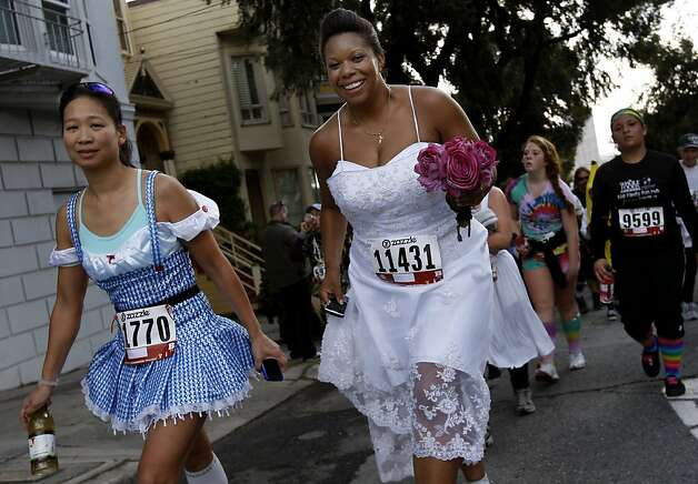 Two women, all dressed up, smiled as they finished Hayes Street hill. The 100th running of the Bay to Breakers race in San Francisco, Calif. featured thousands of people and a few new rules to tame past turmoil Sunday May 16, 2011. Photo: Brant Ward, The Chronicle