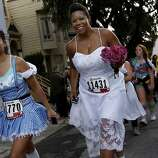 Two women, all dressed up, smiled as they finished Hayes Street hill. The 100th running of the Bay to Breakers race in San Francisco, Calif. featured thousands of people and a few new rules to tame past turmoil Sunday May 16, 2011.
