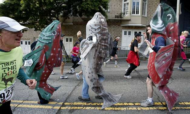 As usual, the fish went the wrong way up the river of runners on Hayes Street. The 100th running of the Bay to Breakers race in San Francisco, Calif. featured thousands of people and a few new rules to tame past turmoil Sunday May 16, 2011. Photo: Brant Ward, The Chronicle