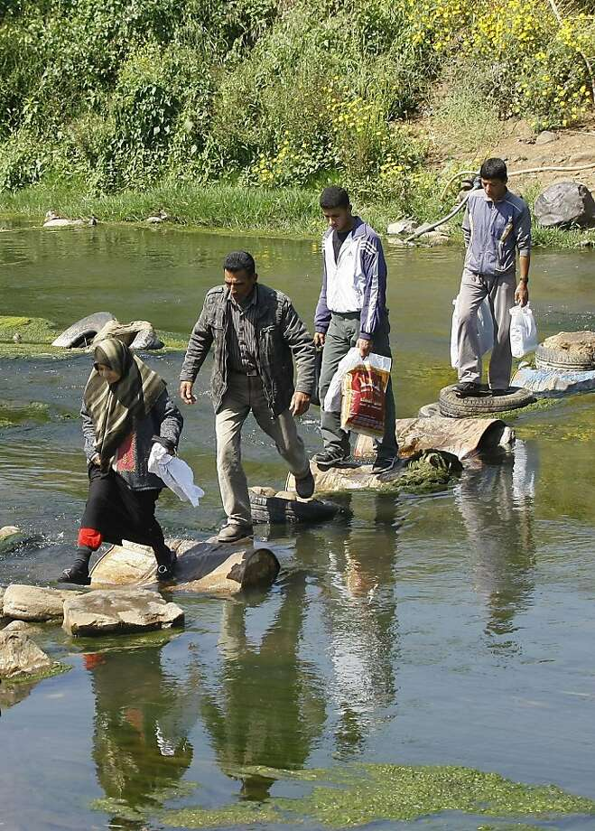 Syrians walk across barrels and tires laid as a makeshift bridge as they cross the Naher al-Kabir river in Wadi Khaled in northern Lebanon from Syrian on May 16, 2011. Hundreds of Syrians fleeing violence in their country poured into northern Lebanon withsome saying they had to wade through rivers and find new routes to avoid gunfire. Photo: Anwar Amro, AFP/Getty Images