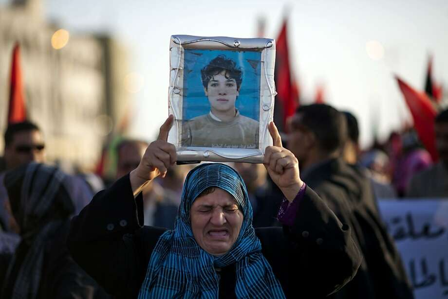 Khalila Ahmed cries as she holds a portrait of her son Marwan Omran, who was killed Feb. 20, 2011 by Moammar Gadhafi security forces, during a protest in Benghazi, Libya, Monday, May 16, 2011.  Luis Moreno-Ocampo, prosecutor of the International CriminalCourt in The Hague, announced Monday that he would seek arrest warrants against the leader of Libya, Moammar Gadhafi, his son Seif al-Islam and the country's intelligence chief on charges of crimes against humanity. Photo: Rodrigo Abd, AP