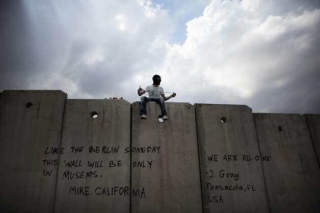 "A masked Palestinian youth sits on top of Israel's controversial separation barrier during clashes with Israeli troops in the West Bank village of Anata on May 15, 2011 as Palestinians marked the ""Nakba"" or ""Catastrophe"" of the 1948 creation of Israel. Photo: Marco Longari, AFP/Getty Images"