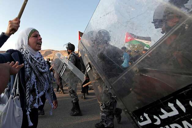 "A Palestinian refugee shouts at Jordanian policemen while raising a baton during a demonstration in Karama, west of the Jordanian capital Amman and near the Jordanian-Israeli border, on May 15, 2011 as police barred 500 people from marching on Israel's border in a show of mourning on ""Nakba (Catastrophe) Day"" over the 1948 creation of the Jewish state. Photo: Khalil Mazraawi, AFP/Getty Images"