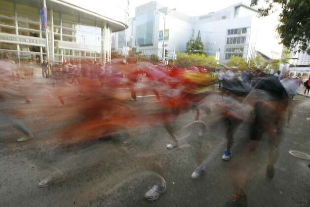 Racers run along Howard Street during the 100th annual Bay to Breakers ...