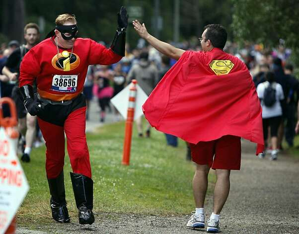 A couple superheroes high-five during the 100th annual Bay to Breakers 12K in San Francisco, Calif., on Sunday, May 15, 2011. Photo: Thomas Levinson, The Chronicle
