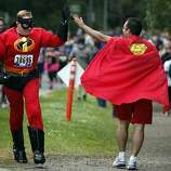 A couple superheroes high-five during the 100th annual Bay to Breakers 12K in San Francisco, Calif., on Sunday, May 15, 2011.