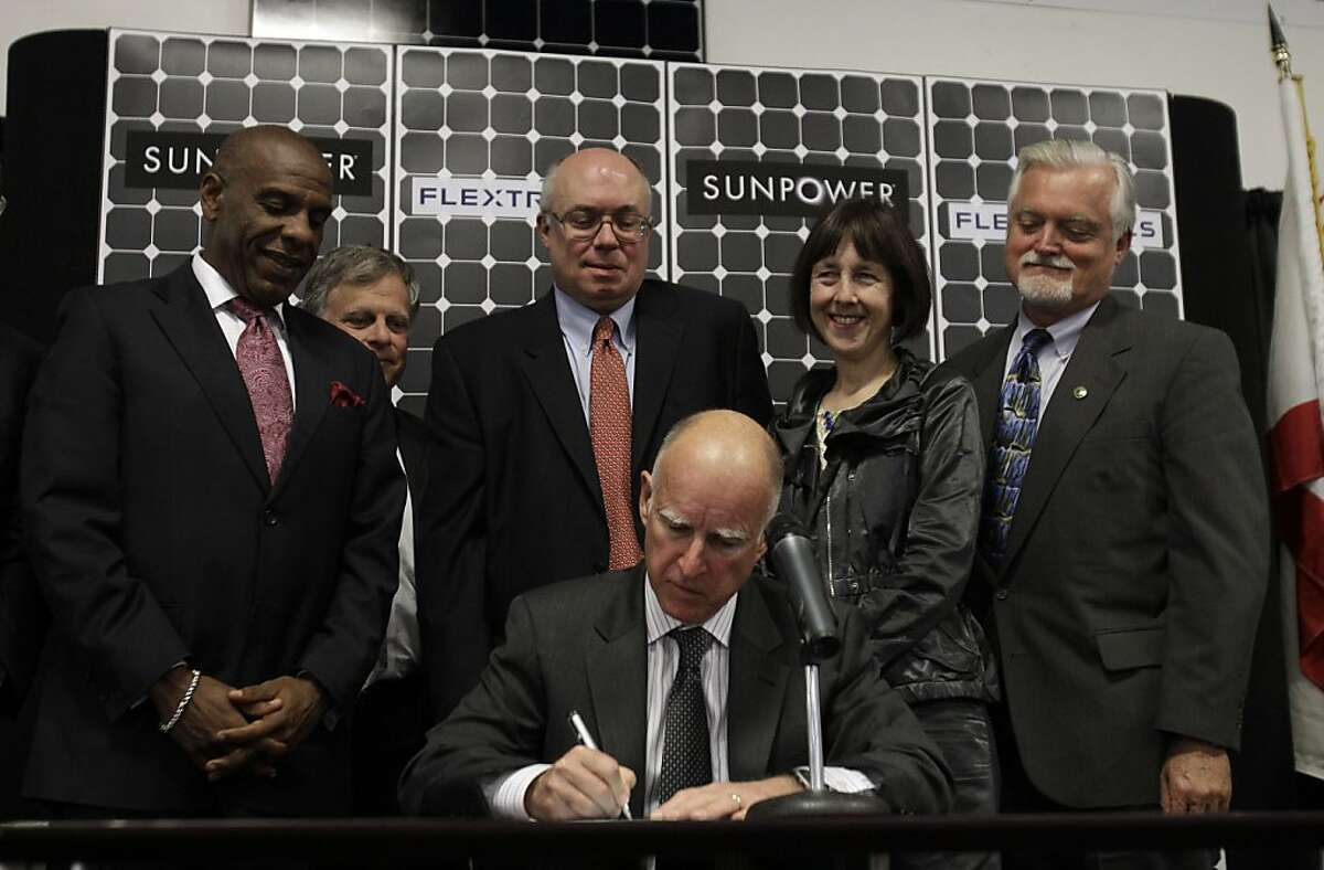 California Gov. Jerry Brown, sitting, signs Senate Bill 2X, as officials including State Senator Joseph Simitian (D-Palo Alto) at center, behind Brown, look on at Flextronics in Milpitas, Calif., Tuesday, April 12, 2011. Gov. Jerry Brown signed legislation Tuesday that would require California utilities to get a third of their power from renewable sources, giving the state the most aggressive alternative energy mandate in the U.S.