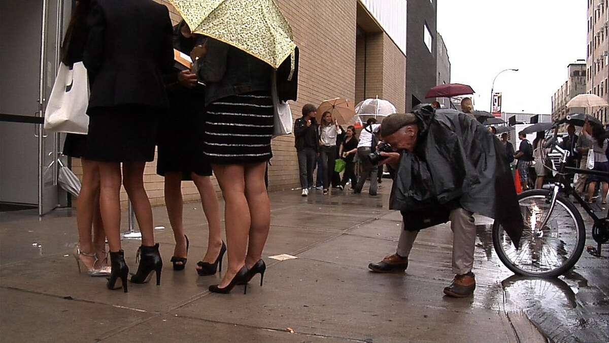Bill Cunningham shooting women attending a fashion show in Chelsea during Fashion Week in New York City from the feature-length documentary,