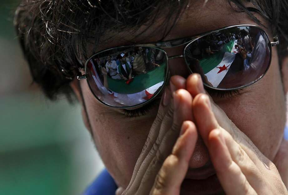 A Syrian protester weeps as others, seen reflected in his sunglasses, chant slogans and hold Syrian flags during a demonstration demanding that Syria's President Bashar Assad step down, in front of the Arab League headquarters building in Cairo, Egypt, Sunday, May 15, 2011. Hundreds of Syrians fled to neighboring Lebanon to escape a violent crackdown against an anti-government uprising that has claimed the lives of more than 800 civilians, Lebanese security officials and a leading human rights group said. Photo: Khalil Hamra, AP