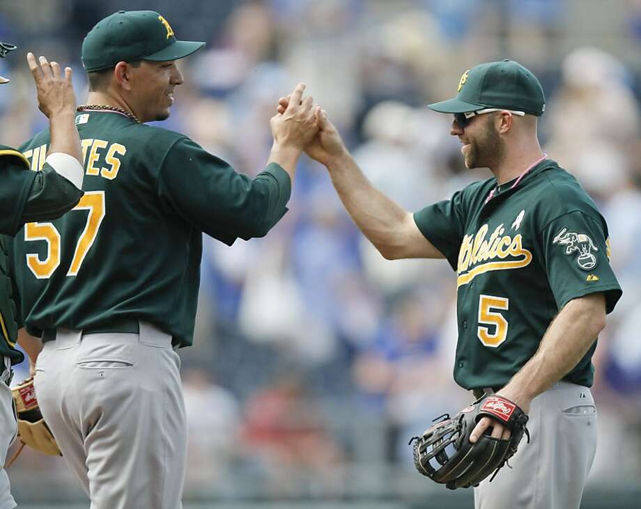 Oakland Athletics relief pitcher Brian Fuentes (57) and teammate Kevin Kouzmanoff (5) celebrate the Athletics' 5-2 win over the Kansas City Royals in a baseball game, Sunday, May 8, 2011, in Kansas City, Mo. Photo: Ed Zurga, AP