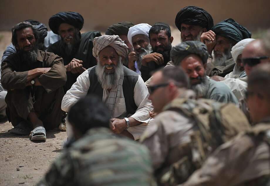 US Marines from Combat Operation Patrol (COP) Bandini and Zaehringer of 2nd Batallion 8 Marine (2/8) Weapons Company 81's Platoon sit together with villagers during a shura (meeting) in Sistani, Helmand Province, on May 12, 2011. About 150,000 foreign troops -- 100,000 of them US forces -- are deployed in Afghanistan in a protracted counter-insurgency campaign against the Taliban, which was ousted in a US invasion in 2001 for its support for Al-Qaeda. Photo: Bay Ismoyo, AFP/Getty Images