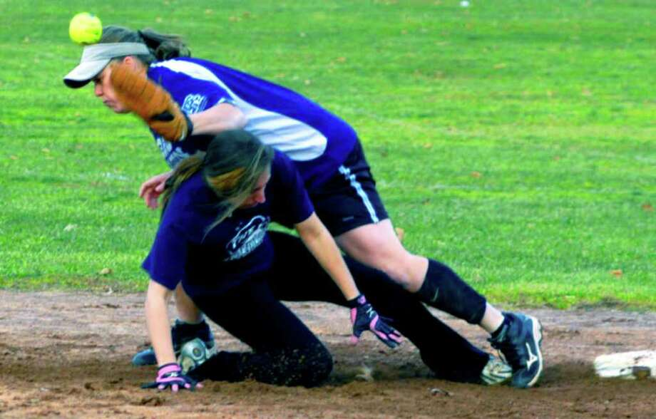 SPECTRUM/Shelby Hilario of Sports Page Cafe encounters B & B Mason second baseman Stephanie Dumas as she retreats to second base during New Milford Parks & Recreation's coed softball championship game at Pettibone School. Nov. 27, 2011 Photo: Norm Cummings