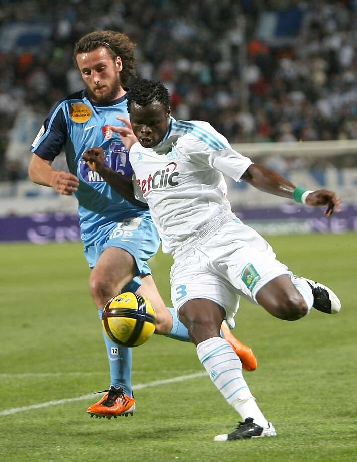 Marseille's Nigerian defender Taye Taiwo Ismaila, right, challenges for the ball with Brest's French defender Paul Baysse  , during their League One soccer match, at the Velodrome Stadium, in Marseille, southern France, Wednesday, May 11, 2011. Photo: Claude Paris, AP
