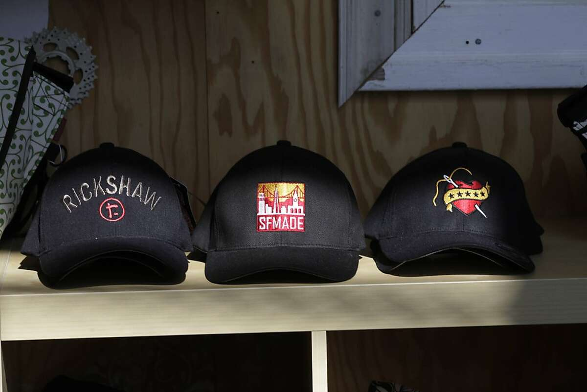 Caps with the SFMADE logo (center) and Rickshaw Bagworks log0 (left and right) are seen at Rickshaw Bagworks on Wednesday February 17, 2010 in San Francisco, Calif.