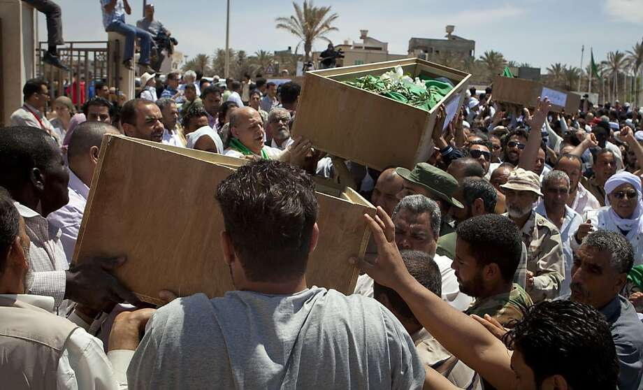 """Mourners carry coffins during funeral for nine of 11 clerics allegedly killed in a NATO airstrike in Tripoli, Libya, Saturday, May 14, 2011. NATO said Saturday it cannot confirm a Libyan government claim that 11 Muslim clerics were killed in an airstrike in eastern Libya but regrets """"any loss of life of innocent civilians"""" whenever it occurs. (AP Photo/Darko Bandic) Photo: Darko Bandic, AP"""