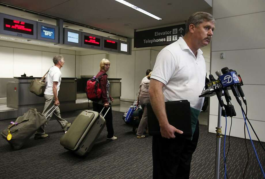 Passengers heading for their flights walk past retired police officer Larry Wright as he describes how he took down a disturbed passenger when he rushed the cockpit door on a flight from Chicago on Sunday night, at a news conference at SFO in San Francisco, Calif. on Tuesday, May 10, 2011. Photo: Paul Chinn, The Chronicle