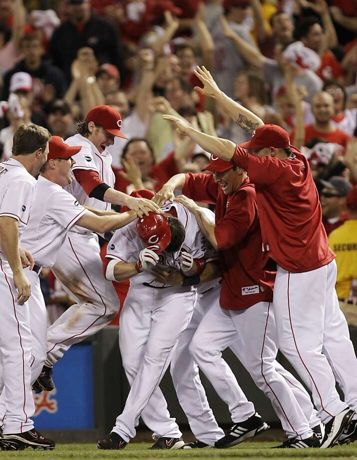 Cincinnati Reds' Joey Votto, center, covers himself as he is mobbed by his teammates after Votto drove in the winning run off St. Louis Cardinals relief pitcher Jason Motte in the bottom of the 10th inning of a baseball game, Friday, May 13, 2011 in Cincinnati. Cincinnati won 6-5. Photo: Al Behrman, AP