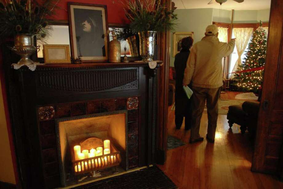 A view of one of the fireplaces on the first floor  at 6 North Pine Ave. in Albany, NY, one of the homes on the Historic Albany Foundation Holiday Tour on Sunday, Dec. 13, 2009.   The home was built in the late 1880's and in the 1930's was divided into a two family home.  Recent work has been done to the house to bring it back to grand single family dwelling.  The home has a three-sided fire place on the first floor and multiple pocket doors.  The front and back porches have also recently been rebuilt.   (Paul Buckowski / Times Union) Photo: PAUL BUCKOWSKI / 00006180B