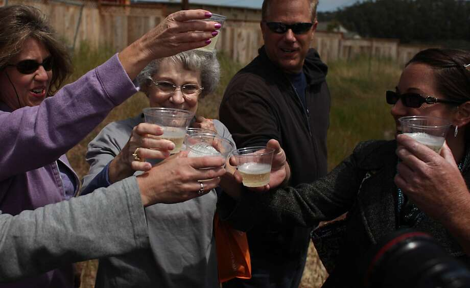 Nancy Hensel (second from left) enjoys a Champagne toast with family at the groundbreaking ceremony to rebuild the Hensels' home in San Bruno on Tuesday. Photo: Lea Suzuki