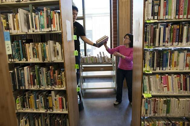 Dennis Lam hand books to Thuhang Phan at the San Francisco Public Library Merced Branch on May 12, 2011 in San Francisco, Calif. Photograph by David Paul Morris/Special to the Chronicle Photo: David Paul Morris, Special To The Chronicle