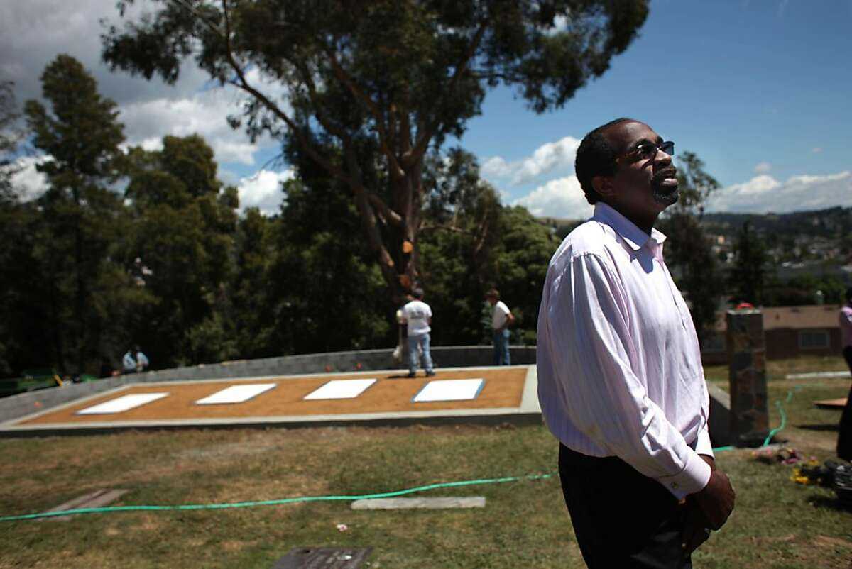 Jim Jones Jr. of Pacifica stands near the markers with the names of the victims of Jonestown shortly after they were placed at the Jonestown memorial still under construction at Evergreen Cemetery in Oakland, Calif., Monday, May 9, 2011.