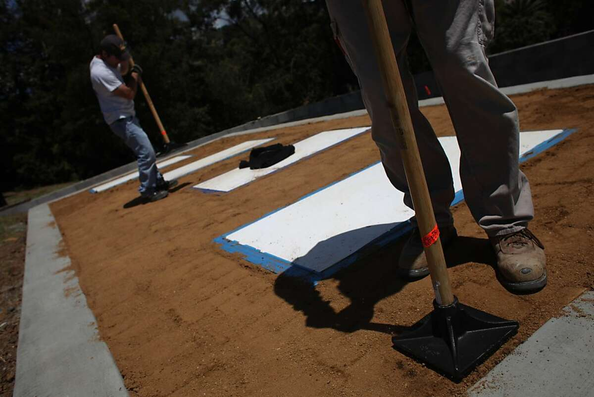 Michael Meyer (l to r) and Jerry Suarez tamp down crushed granite that surround the markers with the names of the victims of Jonestown that were placed at the Jonestown memorial still under construction at Evergreen Cemetery in Oakland, Calif., Monday, May 9, 2011.