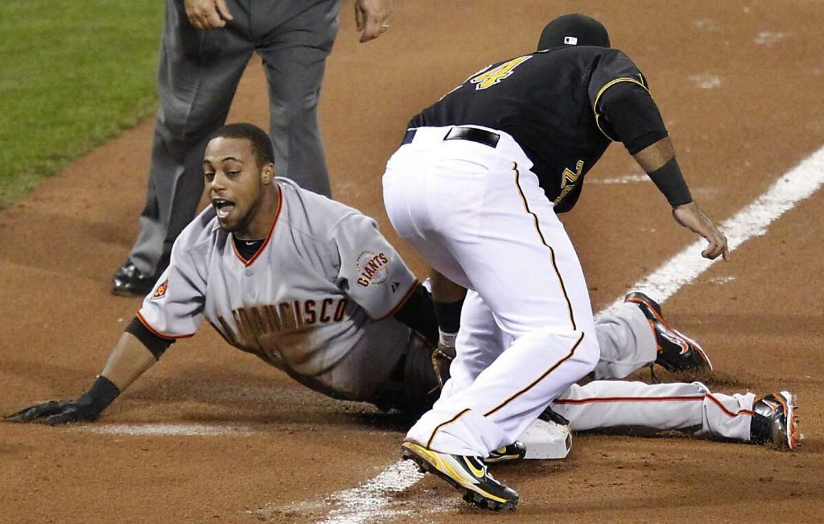 Pittsburgh Pirates third baseman Pedro Alvarez, right, can't get the tag on San Francisco Giants' Darren Ford as he slides safely into third during the 10th inning of a baseball game in Pittsburgh on Tuesday, April 26, 2011. Ford advanced from first to third on a wild pickoff throw by pitcher Joel Hanrahan. The Giants won 3-2 in 10 innings with Ford scoring the deciding run.