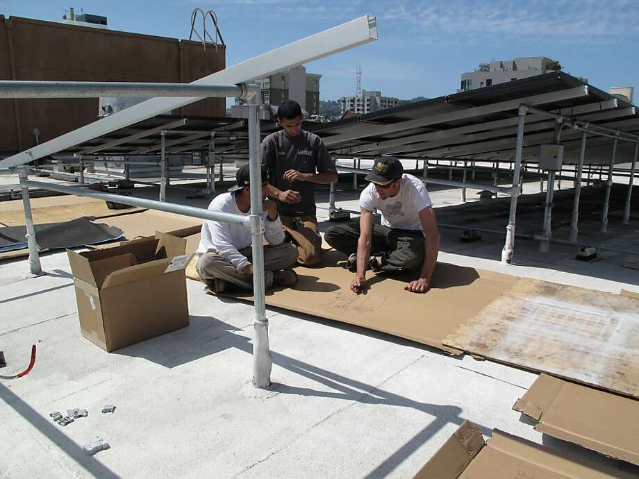 Bailey Smith, lead installer, with Mohamed Ibrahim and Lalo Rangel, two of Luminalt's GoSolarSF certified workers on the roof at Project Open Hand. Mo and Lalo grew up in San Francisco and both are graduates of Asian Neighborhood Design. Photo: Luminalt