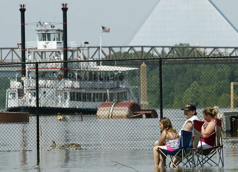 Robert and Carrie Medders and their daughter, Aleigha, 6, left, cool off in the swollen Mississippi River floodwaters as a riverboat passes by Tuesday, May 10, 2011, in Memphis, Tenn. The river crested in Memphis at nearly 48 feet on Tuesday, falling short of its all-time record but still soaking low-lying areas with enough water to require a massive cleanup. Behind them is the Pyramid Arena. Photo: Mark Humphrey, AP