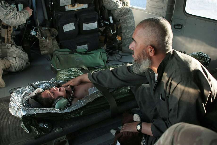 A seven-year-old girl, shot in the back during insurgent attacks in Kandahar, Afghanistan, on Saturday, May 7, 2011, cries as her father, clutching a stuffed toy, comforts her in the back of an American medevac helicopter. The Taliban unleashed a major assault Saturday on government buildings throughout Kandahar, an attack that cast doubt on how successful the U.S.-led coalition has been in its nearly yearlong military campaign to establish security and stability in the former Taliban stronghold. Photo: Colin Perkel, Associated Press