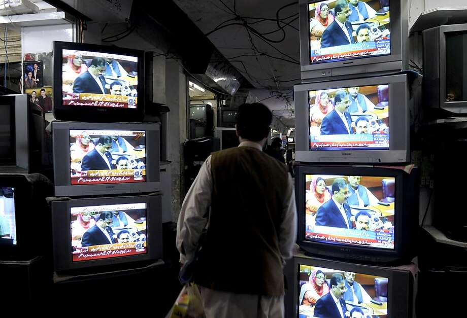 A Pakistani resident walks past a television broadcasting the address of Pakistan's Prime Minister Yousuf Raza Gilani in Quetta on May 9, 2011. Pakistan met US demands for an inquiry into how Osama bin Laden lived for years under the noses of its militarybut refused to be blamed alone for Al-Qaeda or its mastermind. In a 30-minute address to parliament, Prime Minister Yousuf Raza Gilani took veiled swipes at the United States and exonerated Pakistan's military of complicity or incompetence over the world's most-wanted terrorist. Photo: Banaras Khan, AFP/Getty Images