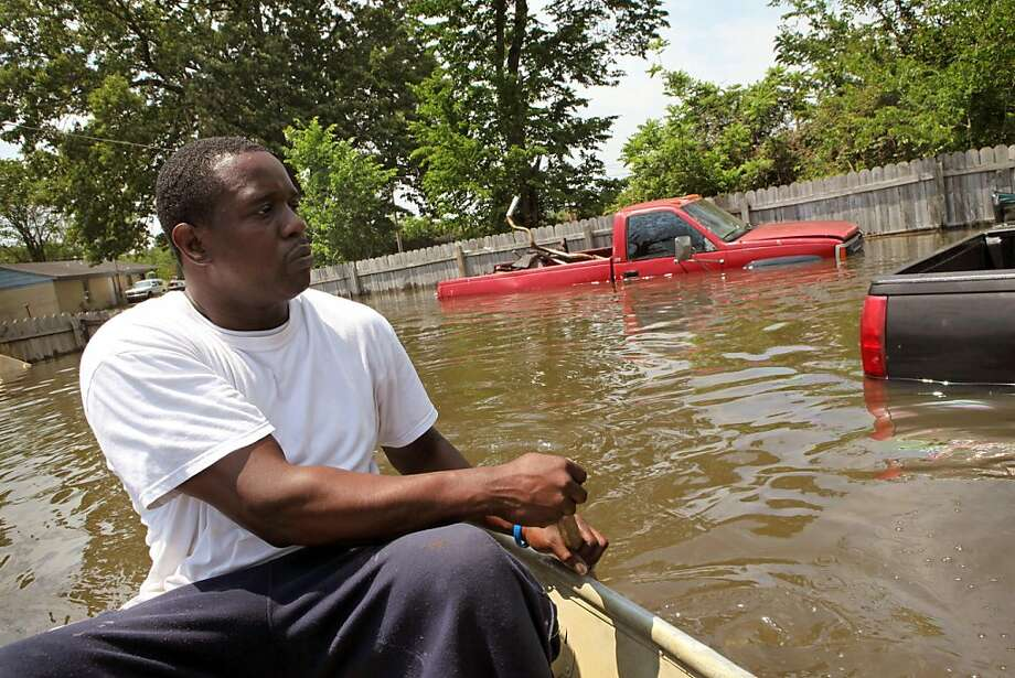MEMPHIS, TN - MAY 09:  Jermaine Jarrett paddles a boat through a flooded yard in his neighborhood May 9, 2011 in Memphis, Tennessee. The Mississippi River is expected to crest at Memphis tonight at 48 feet, which is about 6 inches shy of the record set during the flood of 1937. Officials estimate about 1,300 homes in the city are at risk of suffering dangerous flooding. Heavy rains have left the ground saturated, rivers swollen, and have caused widespread flooding in Missouri, Illinois, Kentucky, Tennessee, and Arkansas. Photo: Scott Olson, Getty Images